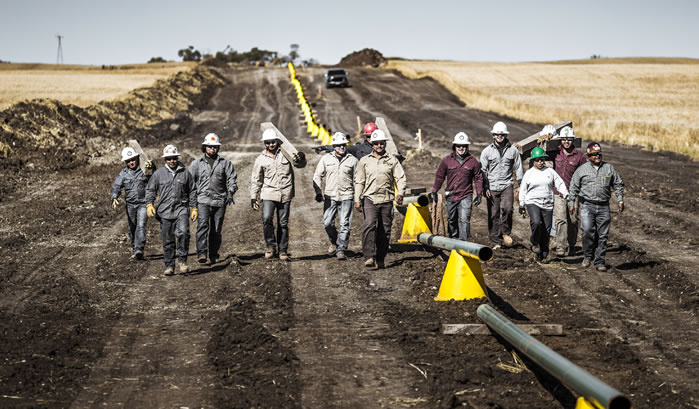 workers walking along pipeline