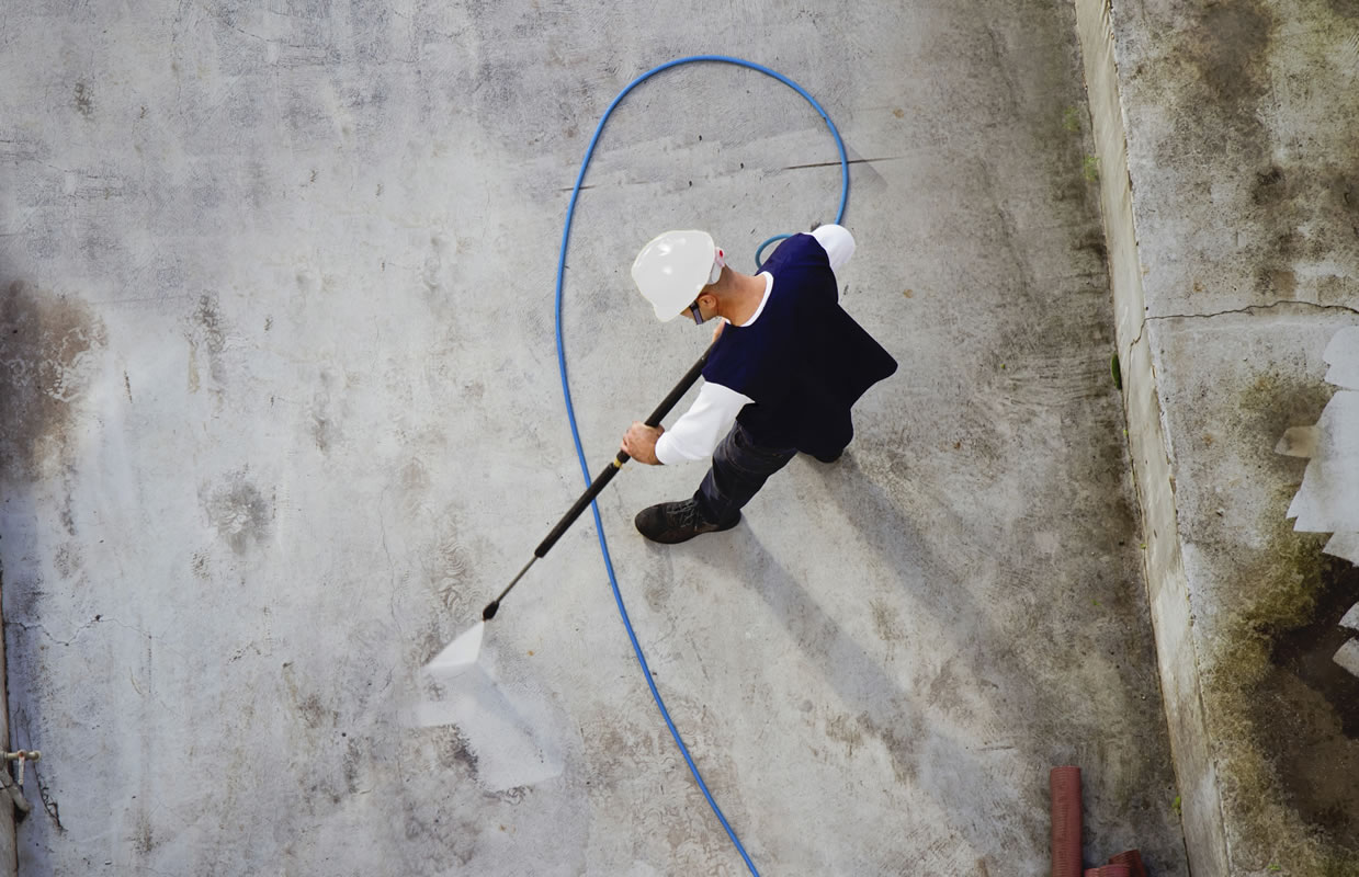 man cleaning with power sprayer