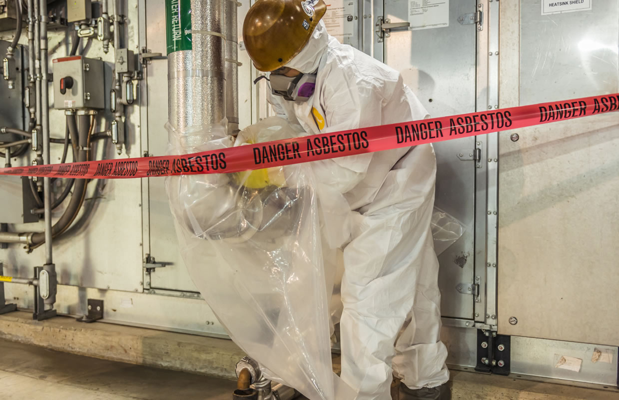 man in safety gear cleaning asbestos