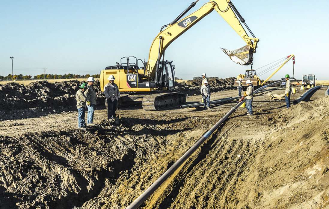 Workers on pipeline with heavy equipment
